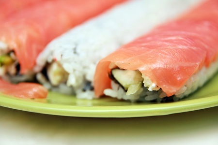 Ready sushi roll on green plate, closeup photo