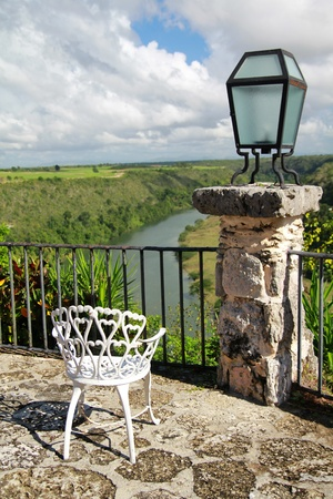Old chair in Altos de Chavon cafe with view on tropical river photo