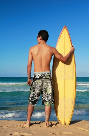 Surfer holding a surf board on beach photo
