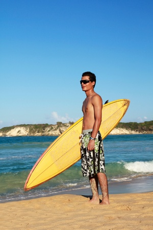 Surfer holding a surfboard on beach