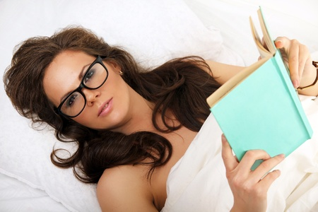 Closeup portrait of young brunette woman in glasses with book on the bed