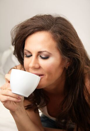 Brunette girl holding white cup of hot drink Stock Photo - 9766040