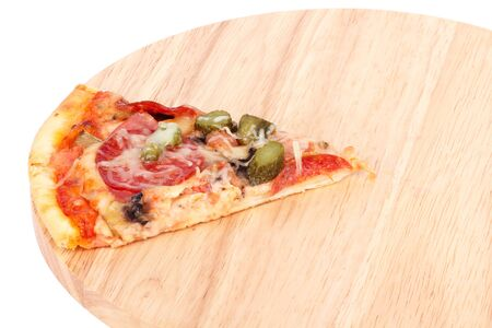 Slice of pizza on wooden cutting board, closeup on white photo