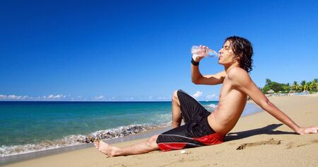 Boy drinking mineral water on beach photo