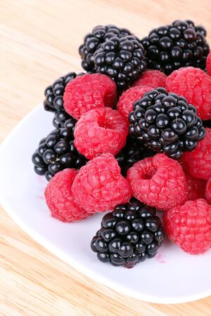 Blackberry and raspberries on white plate, closeup photo