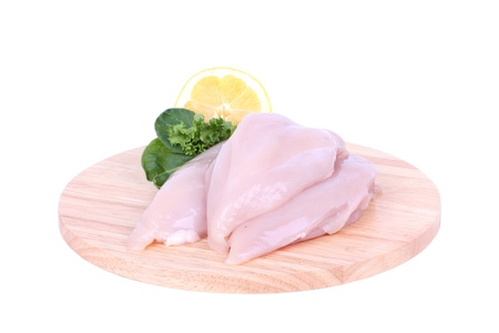 Raw uncooked chicken breast fillet on wooden cutting board, isolated on white