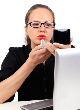 Businesswoman in black office blouse with spectacles looking to mirror using red lipstick photo