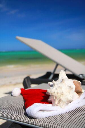 Santa Hat and seashell on chaise longue on caribbean beach Stock Photo - 11311810