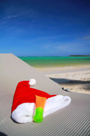 Santa Hat and sun tan on chaise longue on caribbean beach photo