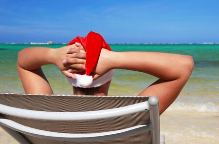 Santa resting on chaise longue on caribbean sea photo