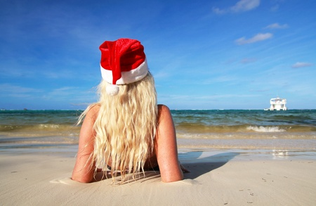 Blond Girl in Red Santa hat on beach photo