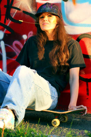 The girl with skateboard sitting against a wall with graffiti background photo