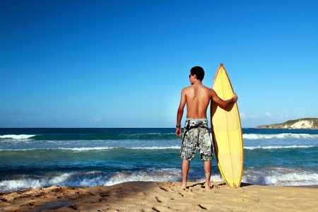 Surfer holding a surf board on tropical beach photo