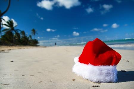 Santa Claus hat on tropical beach, closeup photo