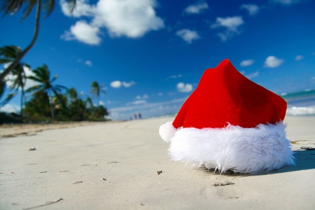 Santa Claus hat on caribbean beach, closeup photo