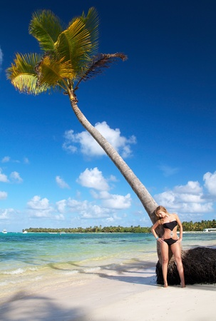 Woman in bikini relaxing on caribbean beach near palm photo