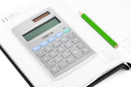 Calculator on notebook, closeup on white photo