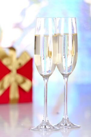 Pair glasses of champagne and present box, closeup on blur background photo