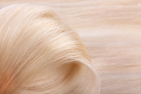 Hair extensions, blond curl closeup photo