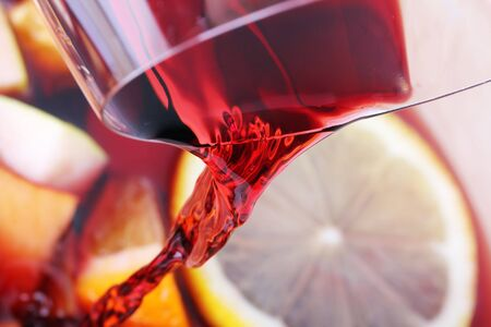 Pouring red wine into juice fruits photo