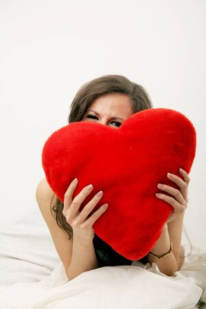 Smiling happy girl in love, holding big red heart photo