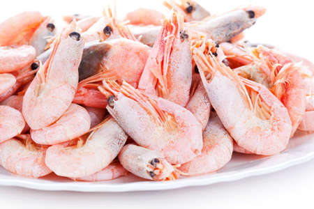 Pile of shrimps on plate, closeup on white background photo