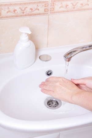 Woman washing hands in bathroom close up photo