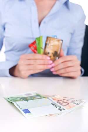 Euro banknotes сloseup and credit cards in business woman hands, sitting in office photo