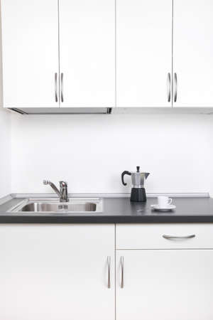 Percolator and one cup of coffee on worktop, kitchen interior photo