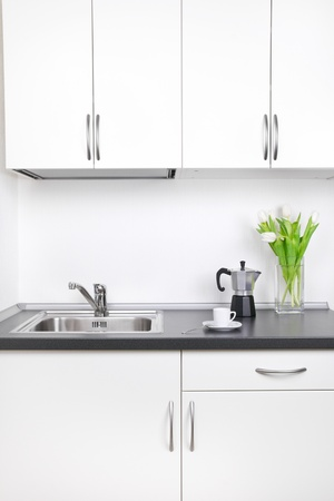 Kitchen interior, cup of coffee, percolator and tulips on worktop