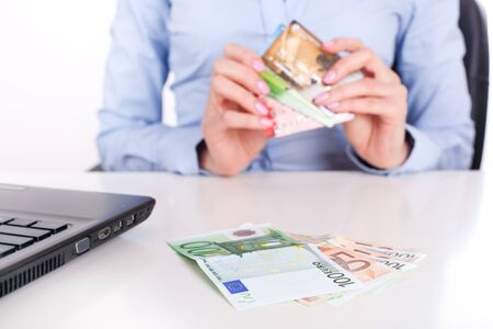 Euro banknotes closeup and credit cards in business woman hands, sitting in office photo