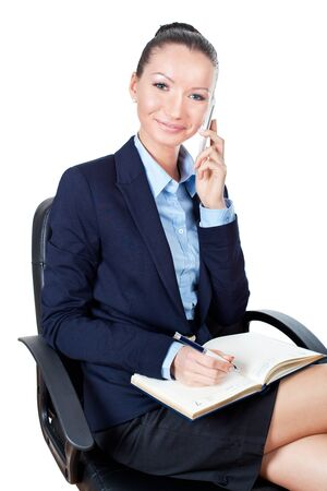 Smilling young business woman sitting on chair and using mobile phone  photo
