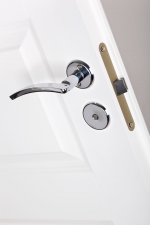 Modern style silver door handle on white door  Stock Photo