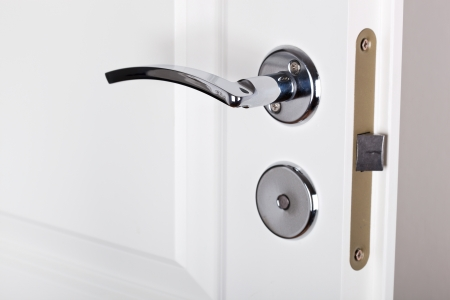 handle: Modern style silver door handle on white door  Stock Photo