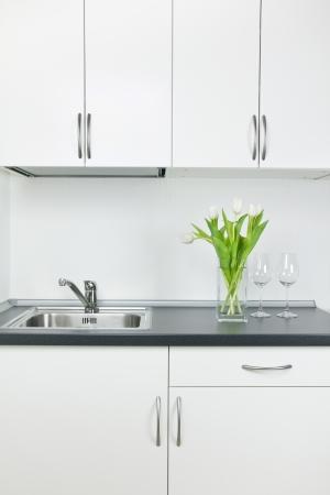 Romantic kitchen interior, empty wineglasses and tulips