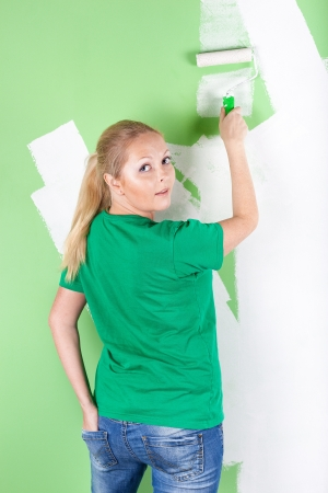 Woman with paint roller in hand, full length portrait photo
