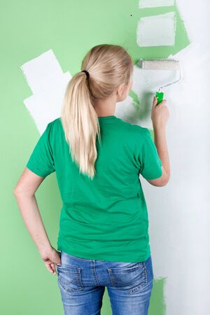 Woman paints green wall, full length portrait photo
