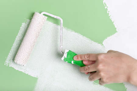 paint roller: Closeup of a hand with paint roller Stock Photo