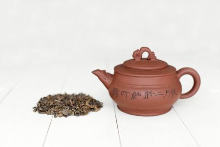 Chinese teapot and pile of green tea on white table photo