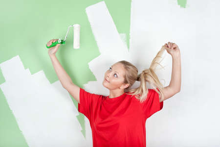 Woman in red t-shirt with paint roller near unfinished wall photo