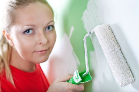 Woman with paint roller in hand near wall photo