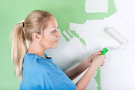 Woman paints the wall, Full length portrait photo