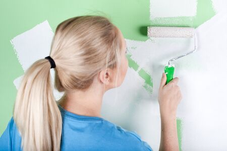 Woman paints the wall, closeup  photo