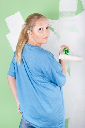Young woman with paint roller in hand, full length portrait photo