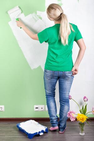 Full length portrait of  a girl  painting the wall photo