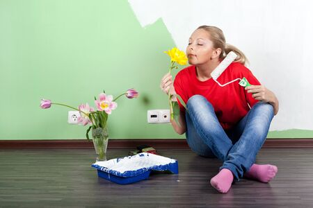 Young woman with flower and paint roller in hands painting interior wall  photo