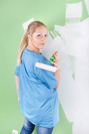 Girl with paint roller in hand, full length portrait photo