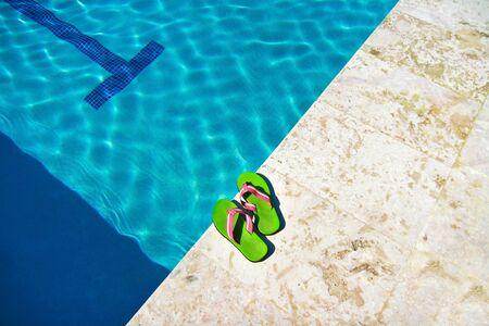 Slippers near swimming pool, tropical resort photo