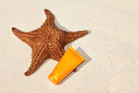 Starfish and suntan tube on sand, closeup  photo