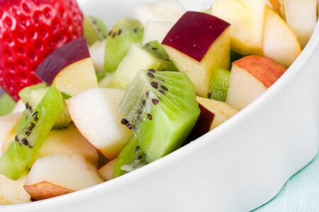 Diet fruit salad in white plate, closeup photo